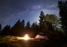 Night camping in mountains. Tourist tent by campfire near forest under blue starry sky, Milky way. Night camping in mountains. Tourist tent by brightly burning stock image