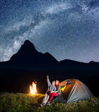 Night camping. Pair of backpackers sitting near tent and fire and enjoying incredibly beautiful starry sky, Milky way Stock Photo