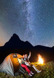 Night camping. Pair of hikers sitting near tent and campfire and enjoying incredibly beautiful starry sky Stock Images