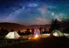 Night camping. Pair hikers stands and holding hands Stock Image