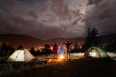 Night camping. Pair tourists stands and holding hands lifting up Stock Photo