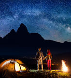 Night camping. Romantic couple holding hands, standing near camp and enjoying starry sky and Milky way Stock Photography