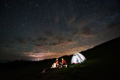 Tourists near campfire and tent under night starry sky Royalty Free Stock Images