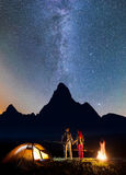 Night camping. Romantic hiker couple - girl and guy holding hands, standing near tent and campfire, enjoying starry sky Stock Image