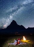 Night camping. Romantic lovers lying near the fire and enjoying incredibly beautiful starry sky. Long exposure Stock Photo
