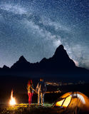 Night camping. Romantic tourist couple - girl and guy holding hands, standing near camp and enjoying starry sky Royalty Free Stock Photos