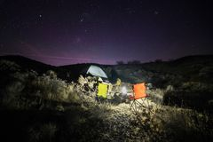 Night camping with tent in desert with scenic night sky with stars.  Stock Photography