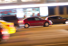 Night car motion. Abstract urban background with night traffic light pattern and motion effect: a red car is going an urban street with high speed Royalty Free Stock Photography