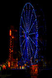 Night Carnival Blue Ferris Wheel, Side View. A summer festival to celebrate July 4th, Independence Day, sets up temporary rides such as this blue ferris wheel Royalty Free Stock Photo