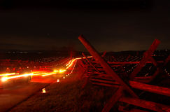 Night Cars. Cars passing at night with split-rail fence royalty free stock photography