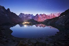 Night at Chamonix in the Alps. Mont Blanc Chamonix France autumn - cold night and starry sky against the backdrop of resort lights, steep peaks of the Alps with stock photo