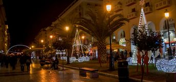 A night christmas walk in the city. A picture of people walking in street, and christmas decoration of christmas trees and street lights,in a towns center,in a Royalty Free Stock Photo