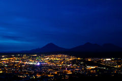 Night city against the dark mountains Royalty Free Stock Photo