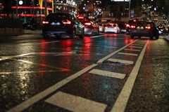 Night city. Asphalt in focus is visible its technical equipment. Asphalt after rain wet royalty free stock image