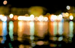 Night City Blur Lights. Coastal city night lights reflected in the dark sea water and break up a lot of bright, colorful highlights Royalty Free Stock Images