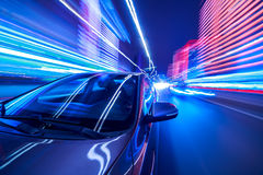 Night city drive by car. Blurred urban look from fast driving car to back side and driver at winter night. Longexposure shot Stock Photo