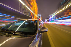 Night city drive by car. Blurred urban look from fast driving car to back side and driver at winter night. Longexposure shot Stock Image