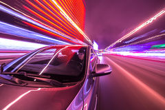 Night city drive by car. Blurred urban look from fast driving car to back side and driver at winter night. Longexposure shot Royalty Free Stock Photo