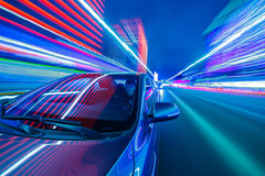 Night city drive by car. Blurred urban look from fast driving car to back side and driver at winter night. Longexposure shot Stock Photography