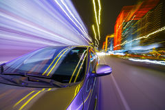 Night city drive by car. Blurred urban look from fast driving car to back side and driver at winter night. Longexposure shot Stock Photos