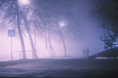 Night city in fog background. Thick mist in dark scary evening city. Dark creepy mystical city in dense fog. Spooky mist royalty free stock image