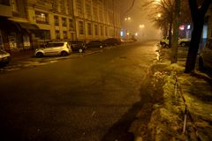 A night city in a fog or haze. Light of street lamps and headlights of passing cars Royalty Free Stock Images