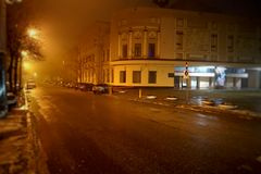 A night city in a fog or haze. Light of street lamps and headlights of passing cars Stock Photo