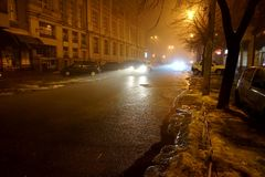 A night city in a fog or haze. Light of street lamps and headlights of passing cars Stock Images