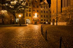 Old Town of Gdansk by Night in Poland. Night in the city of Gdansk in Poland, cobblestone street and square in the Old Town, next to the St. Mary`s Church Stock Image