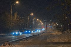 Night city landscape with street lights and urban traffic. In the snow Royalty Free Stock Image