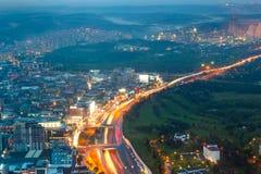 Night City life - motion traffic and illuminated houses Royalty Free Stock Images