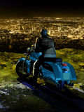 Night city lights. A biker on his motorcycle, contemplates the lights of the city since the height of a mountain Royalty Free Stock Images