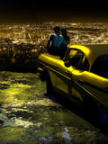 Night city lights. A young couple, close to his car, contemplates the lights of the city since the height of a mountain Stock Photos