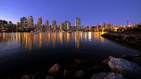 Night city lights reflections in calm water. royalty free stock images