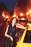 Night city with princess in celebrity style. Fashion and beauty of business lady. Luxury woman in evening dress at night stock image