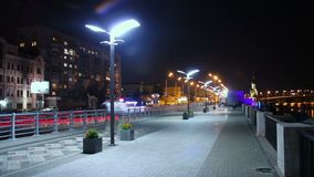 Night city quay, people walking, cars driving, street lights on. Stock footage stock video footage
