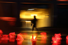 Silhouette of the person in movement. Wet asphalt. Red lights. Stock Photography