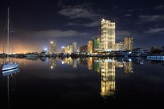 Night city scape on manila bay. Yatch, water, buildings, lights, reflection Royalty Free Stock Image