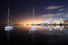 Night city scape on manila bay. Yatch, water, buildings, lights, reflection Royalty Free Stock Photography