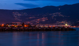 Night city by the sea at the foot of the mountain Stock Photo