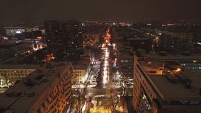 Night city. Shooting with the drone of the air. Bright streets, lights, roads. All in snow. Machines are covered with snow. People walk slowly. Village covered stock photo