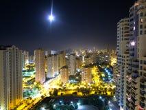 Night city skyline and moon Stock Photos