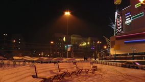 Night city skyline with snow-covered benches, buildings and light illuminating the falling snow. Night winter cityscape with snow-covered benches, lit by yellow stock footage