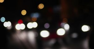 Night city street bokeh. Defocused lights blurred traffic on road. Nightlife abstract blurred shot. Night urban scene. Out of focus stock video footage