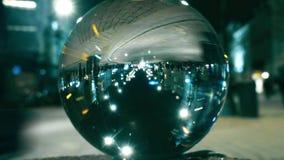Night city street traffic reflecting upside down in the glass ball. Night city street traffic reflecting upside down in the ball stock video