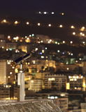 Night city with a telescope. In the foreground, focus is on the telescope Royalty Free Stock Photos
