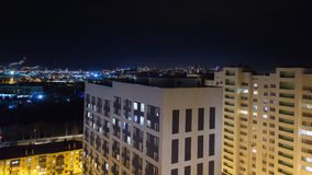 Night city timelapse. Wide angle panorama with residental high-rise and small buildings. Traffic blurred lights on road. Pipes of industrial zone on background stock video