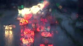 Night city traffic through wet window. Focus on rainy window stock video footage