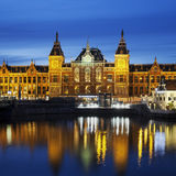Night city view of Amsterdam canal and Centraal Station. Holland, Netherlands Royalty Free Stock Images