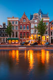 Night city view of Amsterdam canal with dutch houses Stock Photos
